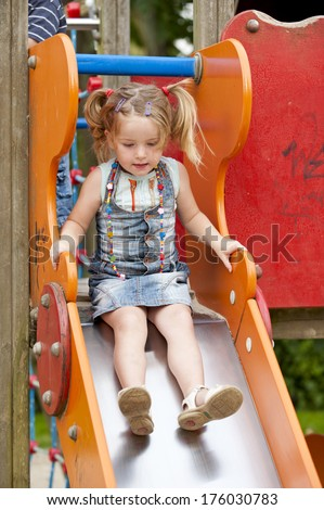 A little girl in pigtails is about to go down a slide. - stock photo