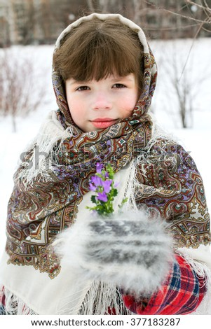 A little girl in russian shawl with few sprout of cowslips - stock photo