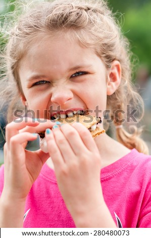 A little girl is eating a s'more made from graham crackers, roasted marshmallows and chocolate.   Her mouth is messy and she is taking a toothy bite of the s'more. - stock photo