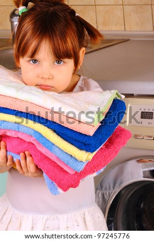 A little girl is going to wash the towels in the washing machine - stock photo