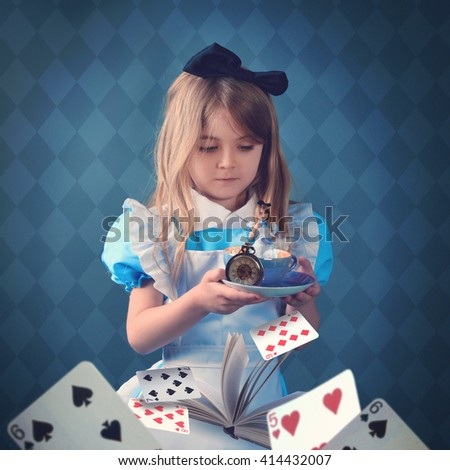 A little girl is holding a teacup with game cards and a book. The child is inside the cup for a surreal fairy tale concept. - stock photo