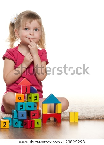 A little girl is lying on the floor near toys - stock photo