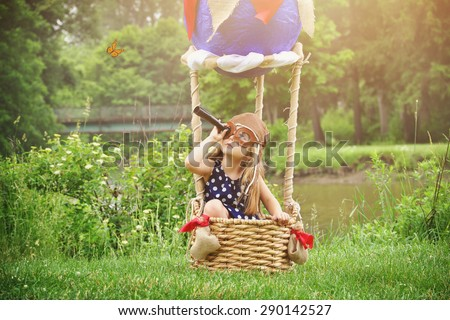 A little girl is sitting in a hot air balloon basket in the park pretending to travel and fly with a pilot hat on for a creativity or imagination concept. - stock photo