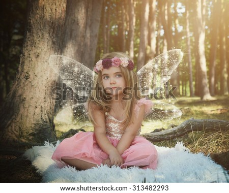 A little girl is sitting in the woods with sparkle fairy wings on pretending to be magical for an imagination or fairy tale concept.  - stock photo