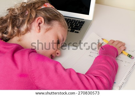A little girl is sleeping with her head on a laptop keyboard.  She is at a desk and her hand rests on a notebook and pencil.  She is wearing a pink sweater and a floral headband. - stock photo