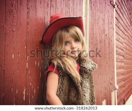 A little girl is standing against a old texture barn with red wood. The child is wearing a cowboy hat and fur jacket for a lifestyle or fashion concept. - stock photo
