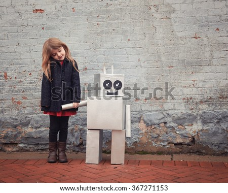A little girl is standing with a metal cardboard robot against a brick wall outside for a friendship or inventor concept. - stock photo