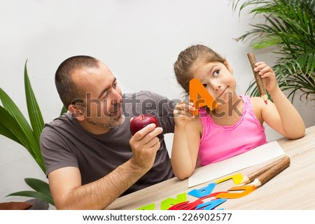 A little girl learns the alphabet playful with her dad - stock photo