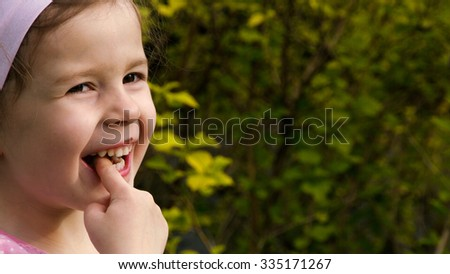 A little girl licking chocolate cream from her finger and laughing - part 1 - stock photo