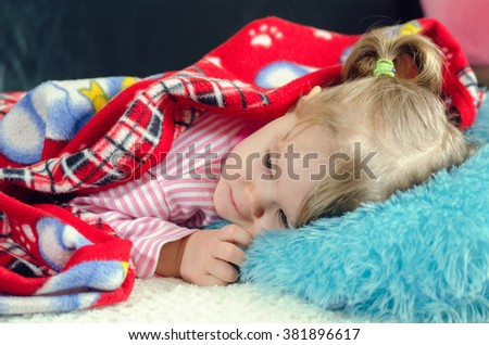 a little girl lies on a bed - stock photo