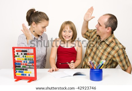 A little girl  next to her parents in fear that she will be beaten if she does not learn. The parents in a position, like they want to slap their daughter - an illustration of aggression in family. - stock photo