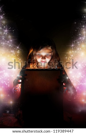 A little girl opening a magic box/present setting the stars free. Christmas or birthday concept �¢?? the magic of gifts. - stock photo