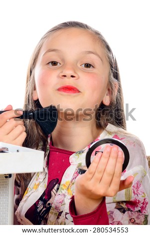 a little girl puts makeup of his mother - stock photo