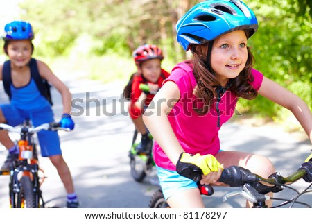 A little girl riding her bike with two friends behind - stock photo