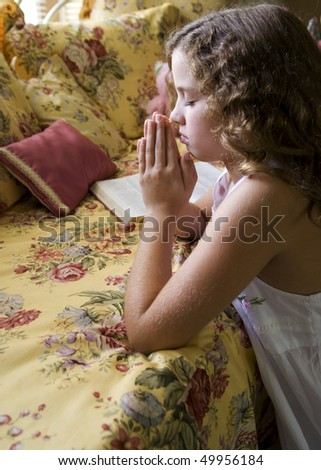 A little girl saying her bedtime prayers. - stock photo