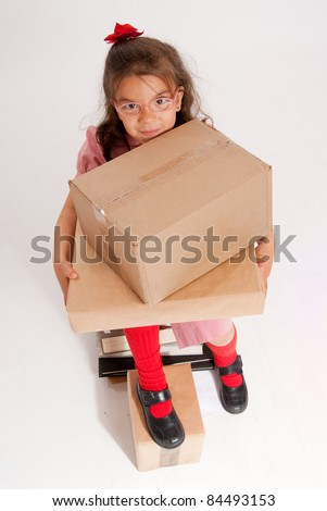 A little girl sitting on a pile of books holding big cardboard boxes - stock photo