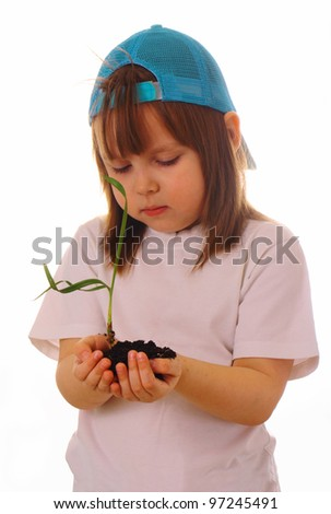 A little girl stands and holds a plant in her hands - stock photo