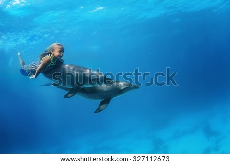 A little girl swimming with pair of dolphins underwater. An ocean life sports extreme design. Kid with marine animals. Red sea diving. - stock photo