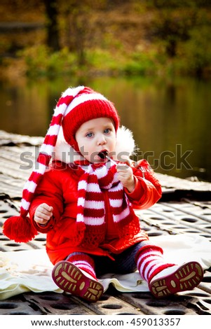a little girl to costume dwarf white and red striped color walks and sits in the woods near water and eats candy on a stick. Dwarf in the woods. The concept of autumn mood - stock photo