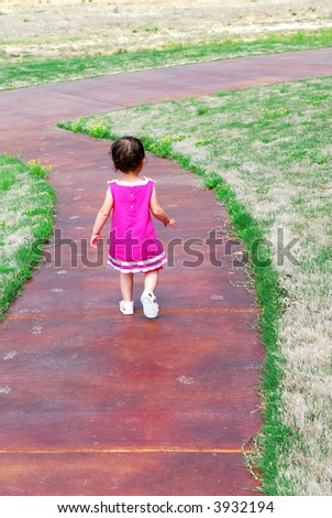 A little girl walking down a sidewalk dressed in a pretty pink dress and sandals. - stock photo