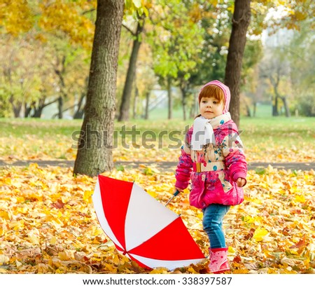 A little girl walking in the park with an umbrella - stock photo