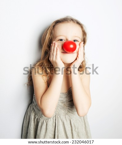 a little girl wearing a clown nose - stock photo
