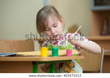 a little girl who draws paints - stock photo