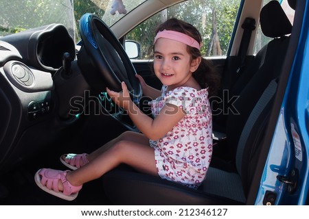 A little girl who drives the car to the game - stock photo