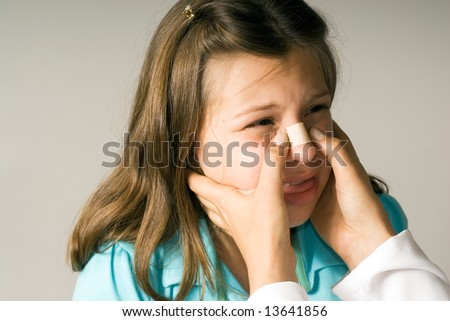 A little girl winces as she gets a band-aid applies to her nose. She is feeling afraid and hopes it won't hurt. Horizontally framed photograph - stock photo