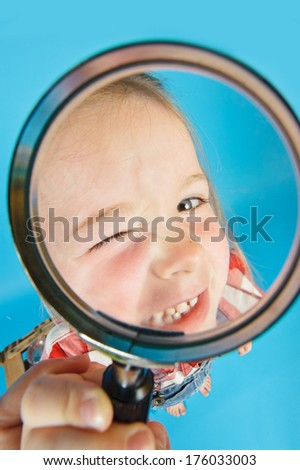 A little girl winking into a magnifying glass with one eye closed . - stock photo