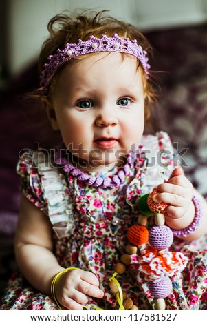 a little girl with a beautiful scarf on his head holds the beads to develop motor skills - stock photo