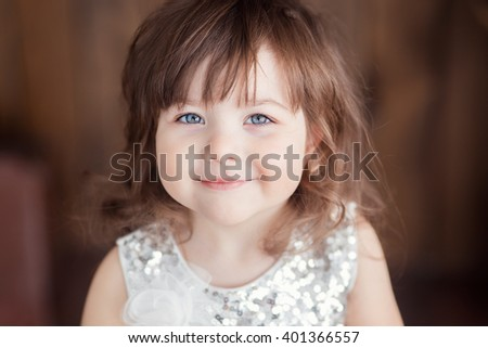 a little girl with brown hair in a white dress close-up portrait against a dark background - stock photo