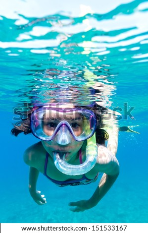 a little girl with mask exploring underwater in the Mediterranean Sea - stock photo