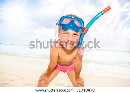 a little girl with snorkel and diving mask at the beach - stock photo
