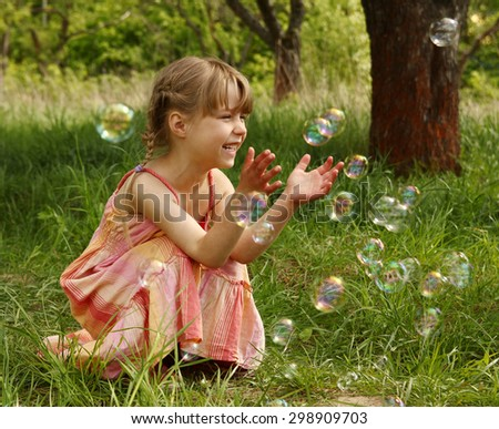 a little girl with soap bubbles girl - stock photo