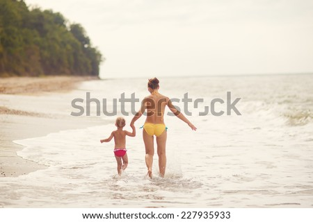 A little happy beautiful girl and her young mother in a swimsuit walking on the sea shore on a warm summer day - stock photo