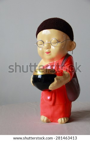 A little monk ,wearing glasses ,holding monk's alms-bowl ,standing alone on a table ,gray color background   - stock photo