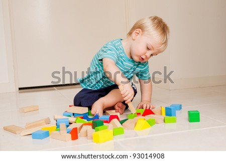 A little 15 month old boy playing with colorful blocks indoors. - stock photo