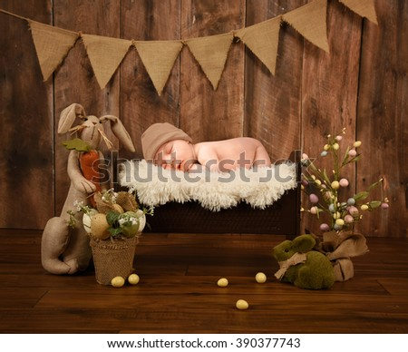 A little newborn baby is sleeping in a white fur bed on a studio rustic wood background with Easter eggs and a bunny for a holiday or love concept. - stock photo