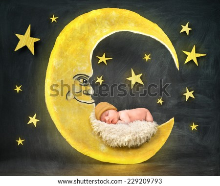 A little newborn baby is sleeping on a paper cutout of a yellow moon with stars in the background for a bedtime or sleep concept. - stock photo