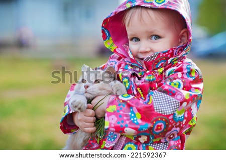 A little pretty girl in a bright jacket holding a cat close-up on a spring day. Kids and nature - stock photo