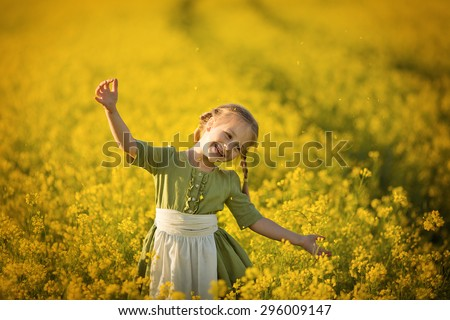 A little pretty girl in a green Bavarian dress with a white apron picking flowers in the field of flowering yellow mustard on a sunny summer day. Kids and nature. Children in country. Beautiful flora - stock photo