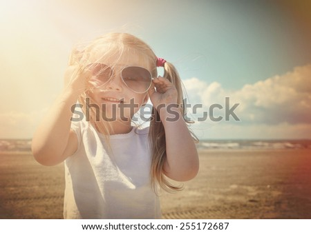 A little retro girl in pigtails is wearing sunglasses at a sandy beach with warm sun shine on her face for a vacation or season concept. - stock photo