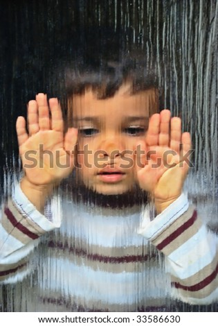A little sad kid looking through glass - stock photo