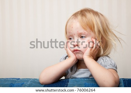 a little sick girl is sitting near the bed - stock photo