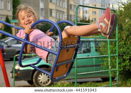 A little smiling girl enjoying swinging in a playground of an apartment house's court yard  - stock photo