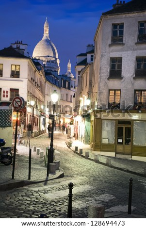 A little street called Rue Norvins at night in Montmartre (Paris, France). Sacre-Coeur in the background. - stock photo
