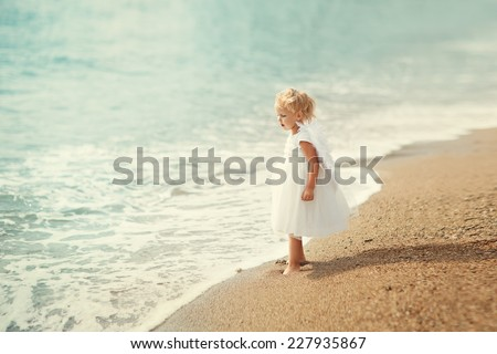 A little sweet blonde girl in a white dress and small wings like an angel standing on the sea shore on a warm summer day - stock photo