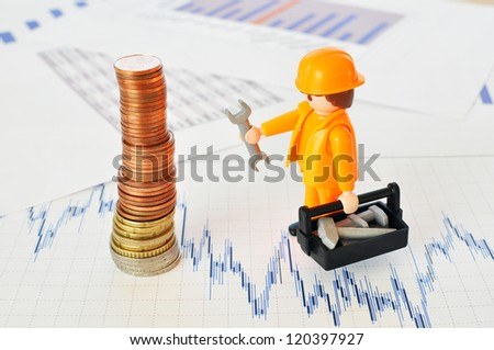 A little worker at a pyramid of coins against financial reports - stock photo