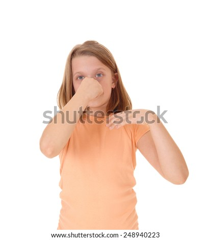 A little young girl standing for white background holding her nose closed for the bad smell around her.  - stock photo